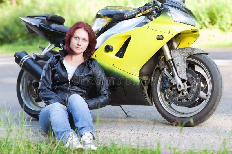 Donna che si siede vicino alla bici fotografie stock