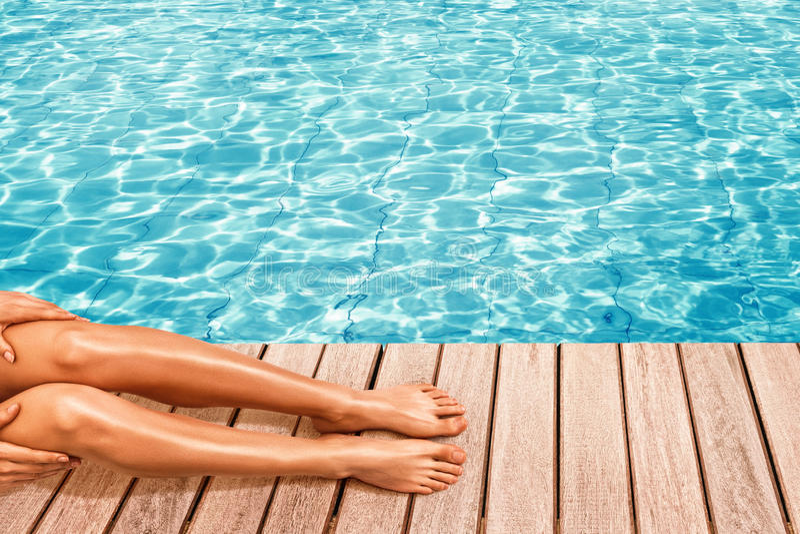 Donna che si siede vicino alla piscina fotografie stock libere da diritti