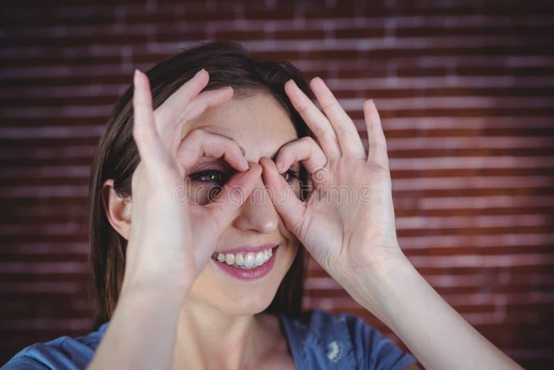 Donna che si tiene per mano come binocolo fotografia stock libera da diritti