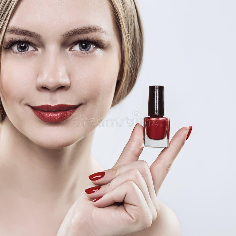 Donna che si tiene per mano con una bottiglia di smalto rosso, il rossetto rosso sulle sue labbra e le unghie rosse immagini stock