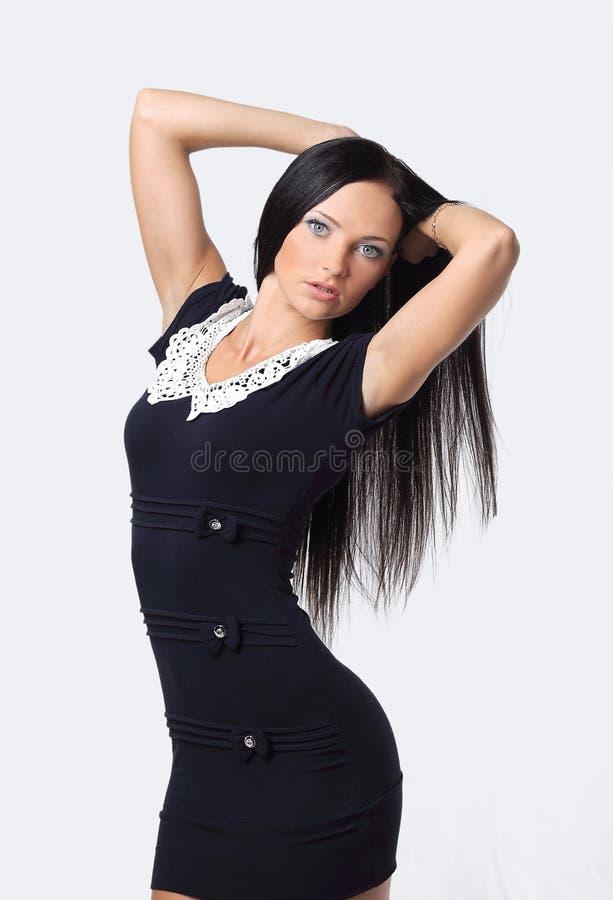 Donna che si tiene per mano dietro la testa, fondo isolato immagini stock libere da diritti