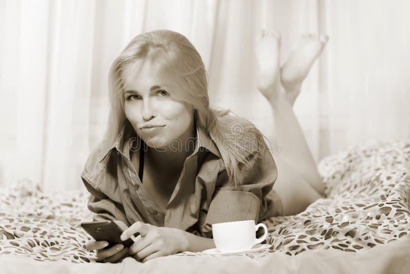 Donna che si trova al letto e che per mezzo del telefono cellulare e che prende offesa fotografia stock libera da diritti