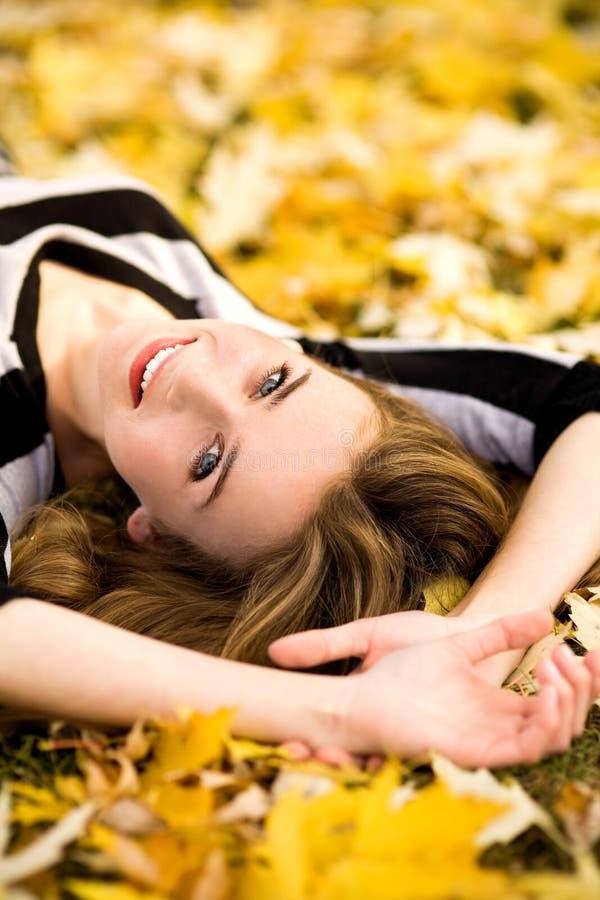 Donna che si trova giù in fogli di autunno fotografia stock libera da diritti