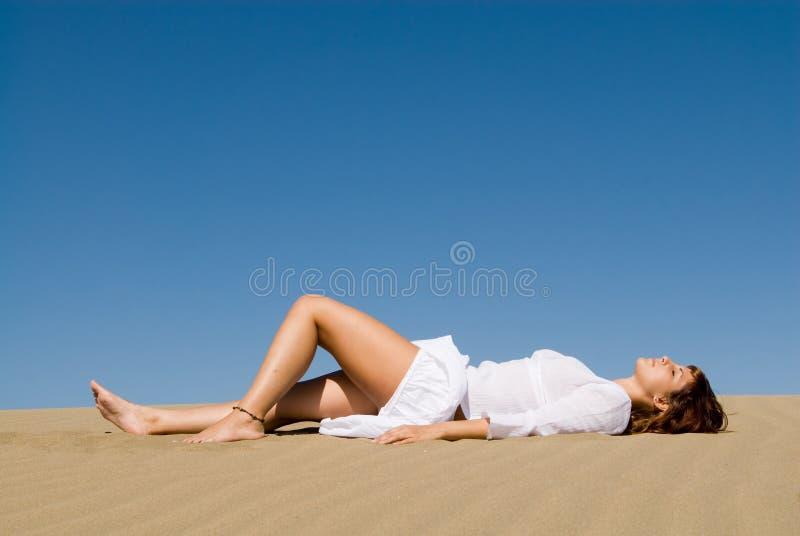 Donna che si trova nella sabbia fotografia stock libera da diritti
