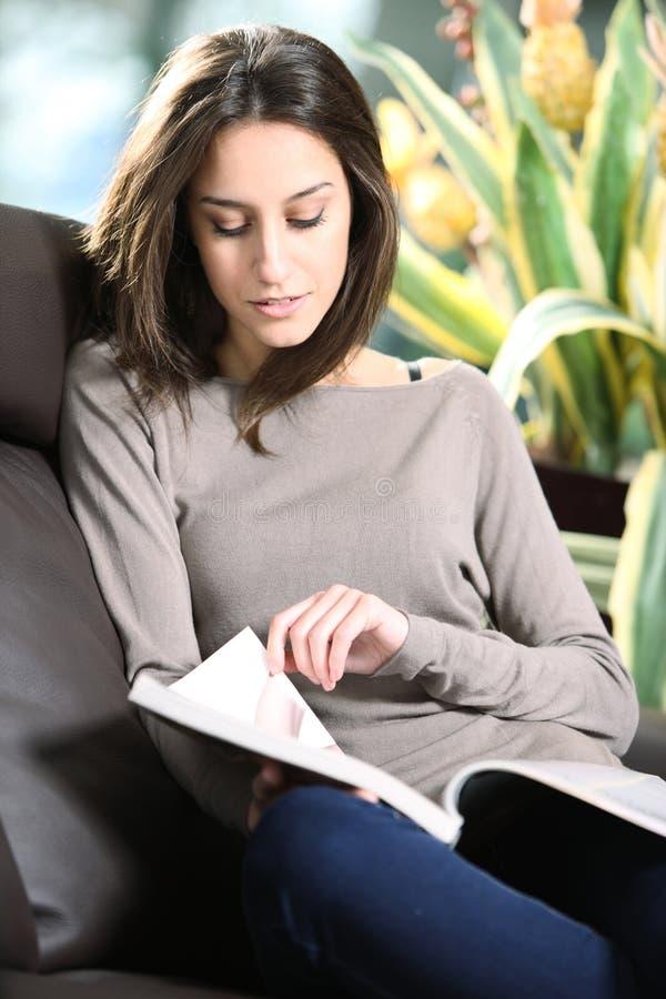 Donna che si trova su un sofà che legge uno scomparto. immagine stock