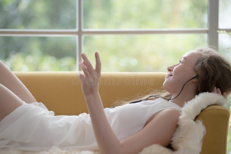 Donna che si trova su uno strato e che ascolta la musica sul suo telefono cellulare fotografia stock libera da diritti
