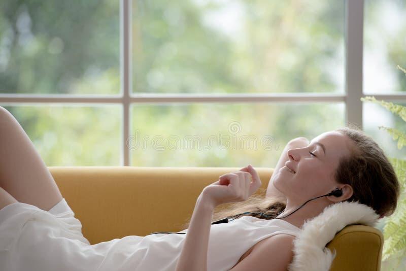 Donna che si trova su uno strato e che ascolta la musica sul suo telefono cellulare immagine stock