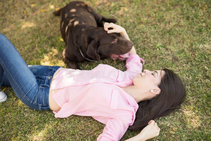 Donna che si trova sul cane di coccole dell'erba fotografie stock libere da diritti