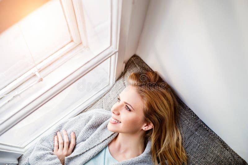 Donna che si trova sul davanzale della finestra, guardante dalla finestra fotografia stock