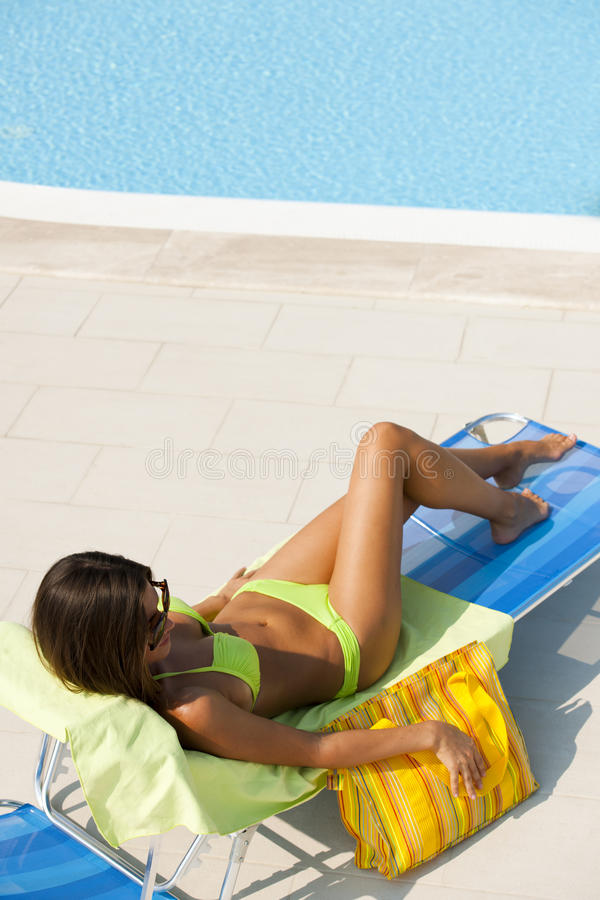 Donna che si trova sul deckchair dalla piscina immagine stock