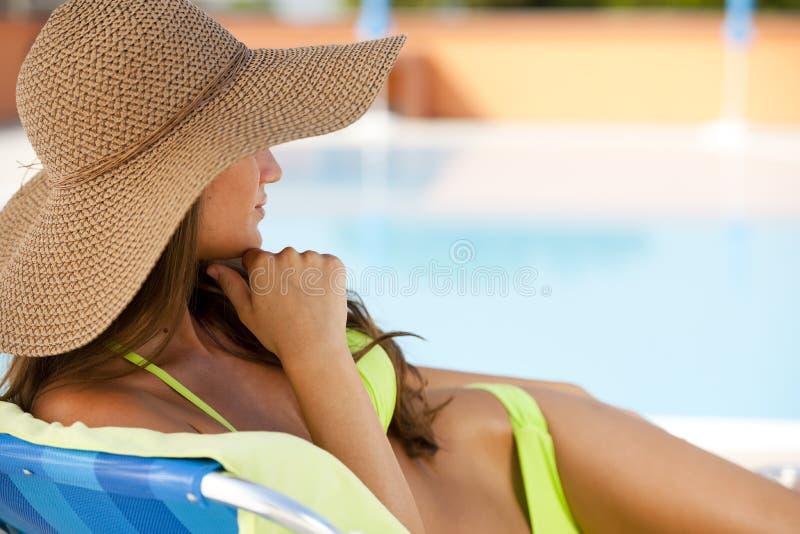 Donna che si trova sul deckchair dalla piscina fotografie stock libere da diritti