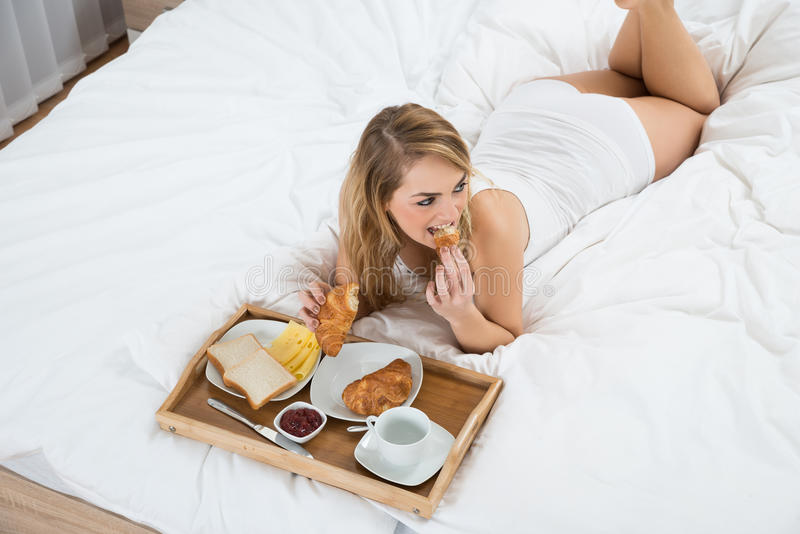 Donna che si trova sul letto che mangia prima colazione fotografia stock libera da diritti