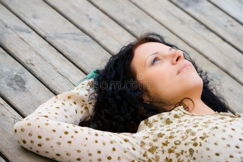 Donna che si trova sul pavimento di legno fotografia stock