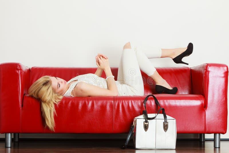 Donna che si trova sul sofà che presenta borsa bianca fotografie stock libere da diritti