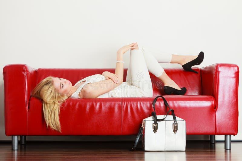 Donna che si trova sul sofà che presenta borsa bianca fotografia stock