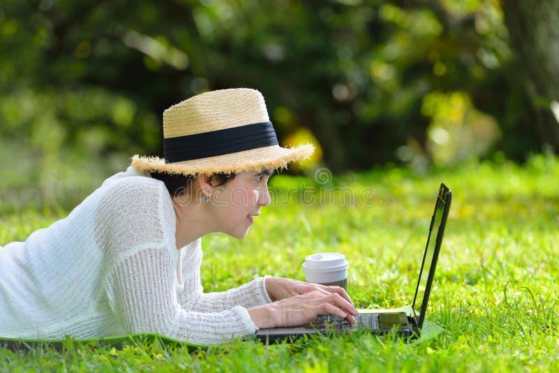 Donna che si trova sull'erba verde facendo uso del computer portatile fotografie stock libere da diritti