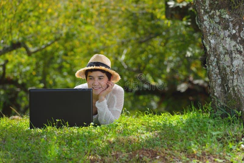 Donna che si trova sull'erba verde facendo uso del computer portatile nel parco fotografie stock