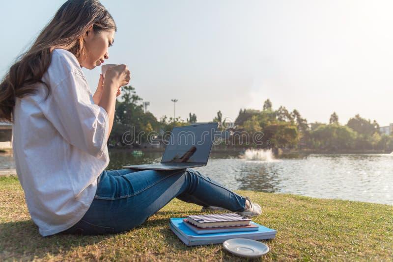 Donna che si trova sulla lettiera su erba verde con la compressa durante il picnic nel parco fotografie stock