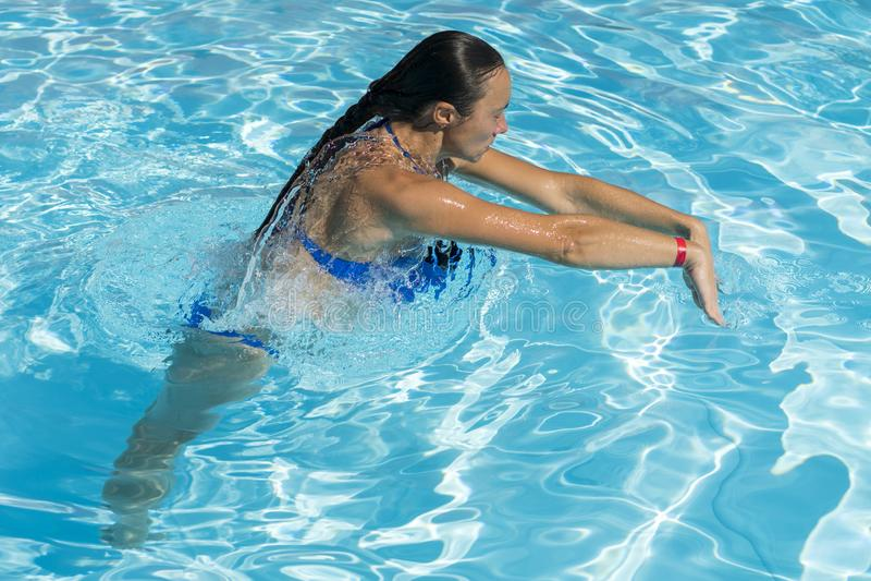 Donna che si tuffa la piscina Giovane bello nuoto della ragazza nello stagno Rilassamento castana in acqua calda chiara il giorno fotografia stock libera da diritti