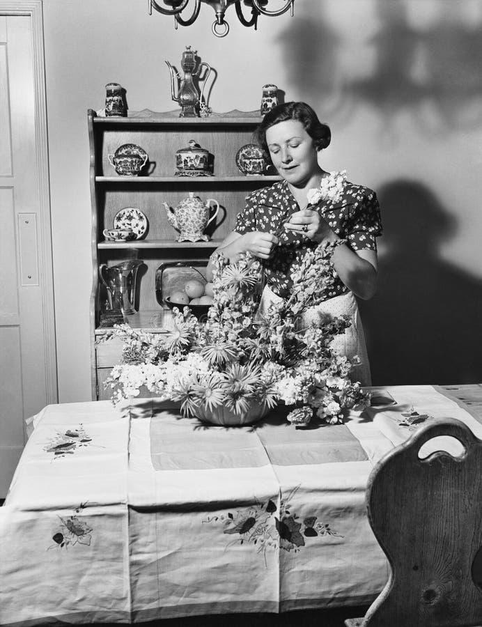 Donna che sistema i fiori a casa (tutte le persone rappresentate non sono vivente più lungo e nessuna proprietà esiste Garanzie d immagini stock