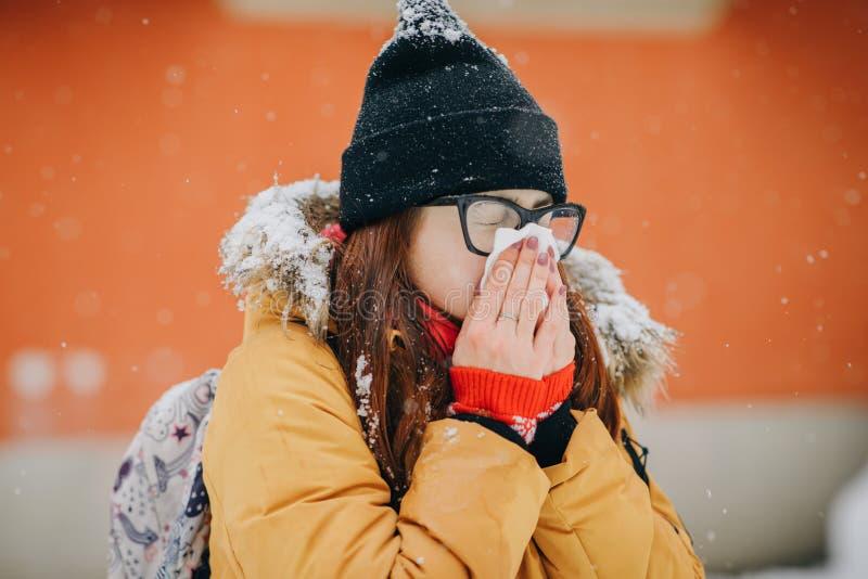 Donna che soffia il suo naso nel fazzoletto Giovane donna che si ammala con l'influenza in un giorno di inverno immagine stock libera da diritti