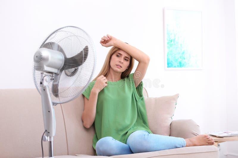 Donna che soffre dal calore davanti al fan immagine stock