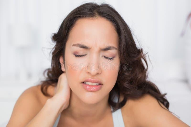 Donna che soffre dal dolore al collo con gli occhi chiusi fotografie stock