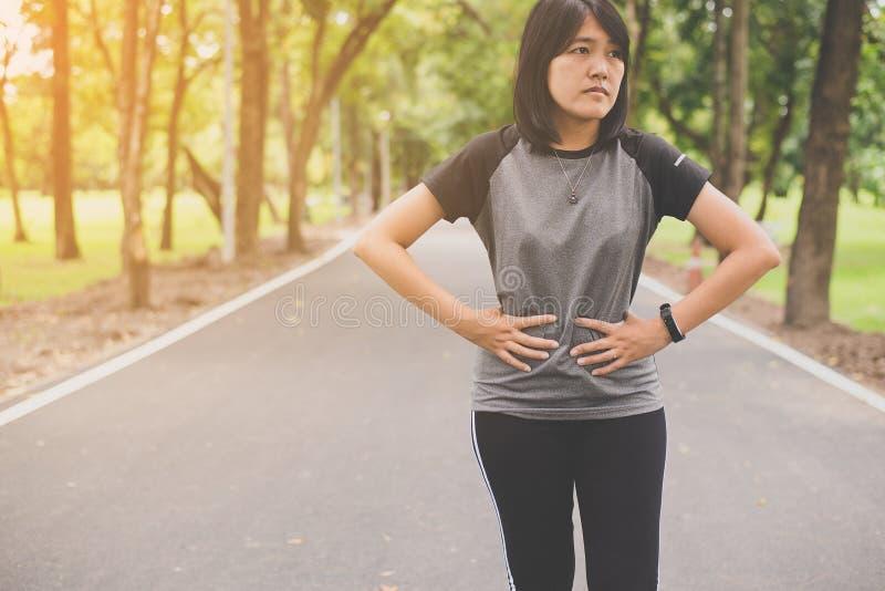 Donna che soffre dal dolore in crampi di stomaco dopo pareggiare e l'allenamento di funzionamento di esercizio di sport all'apert immagine stock libera da diritti