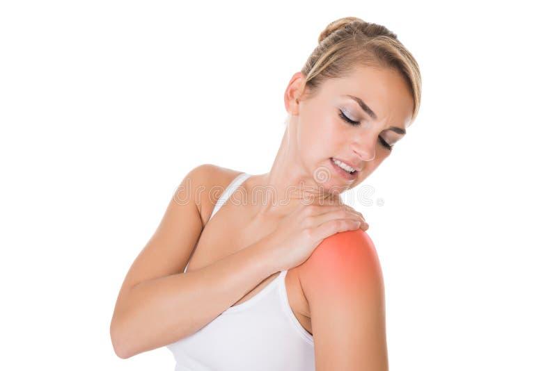 Donna che soffre dal dolore della spalla immagini stock libere da diritti