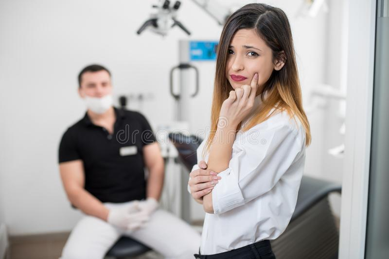 Donna che soffre dal dolore di denti terribile, guancia commovente con la mano alla clinica dentaria Mal di denti femminile di se immagine stock