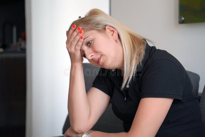 Donna che soffre dal dolore di emicrania di emicrania a casa sul sofà Problema sanitario, sforzo e depressione Testa femminile de immagini stock