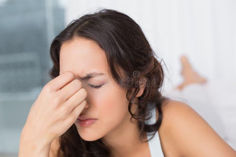 Donna che soffre dall'emicrania con gli occhi chiusi a casa fotografie stock