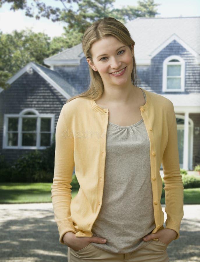 Donna che sorride alla macchina fotografica all'esterno della sua casa fotografie stock libere da diritti