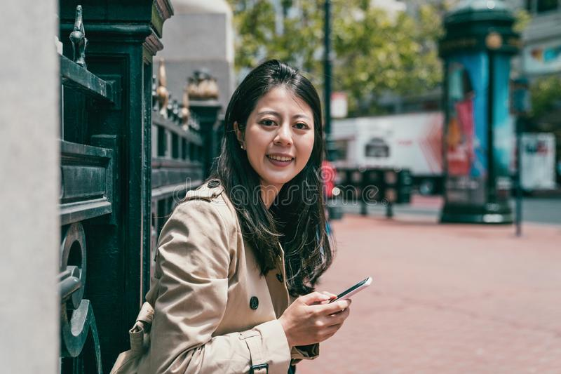Donna che sorride alla macchina fotografica e che tiene smartphone immagini stock libere da diritti