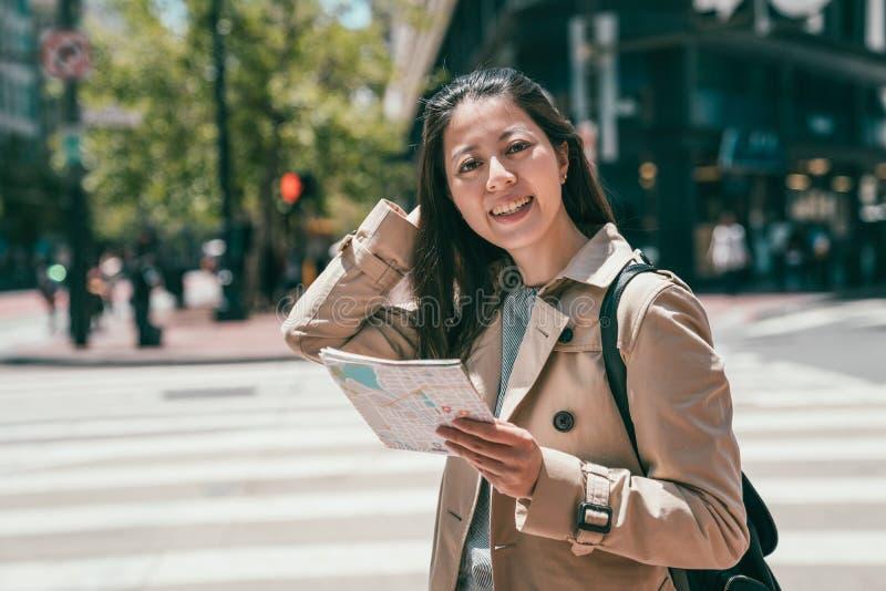 Donna che sorride alla macchina fotografica e che tiene una mappa immagini stock libere da diritti