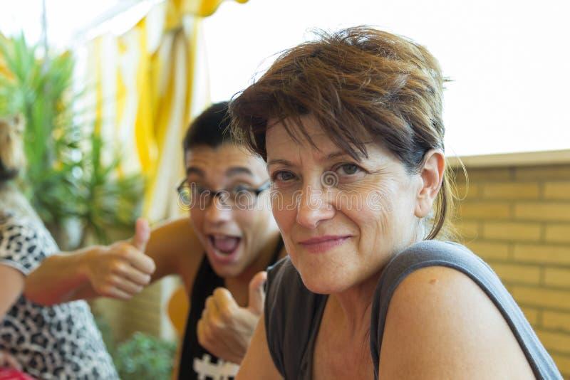 Donna che sorride leggermente ed suo figlio dietro scherzare immagini stock libere da diritti