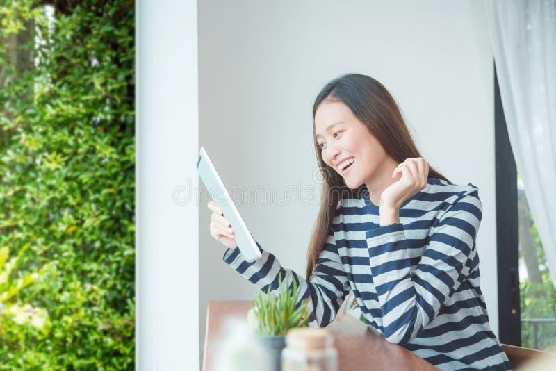 Donna che sorride mentre per mezzo del computer della compressa fotografia stock libera da diritti