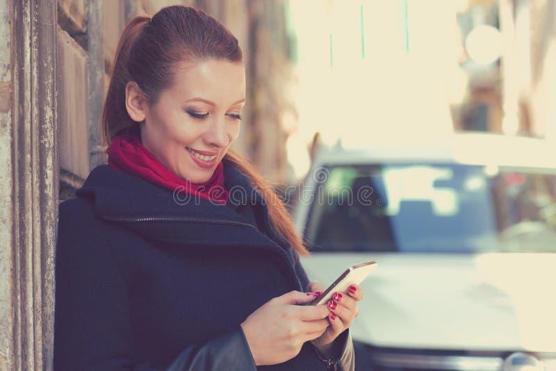 Donna che sorride tenendo un telefono cellulare che sta all'aperto accanto alla nuova automobile immagini stock libere da diritti