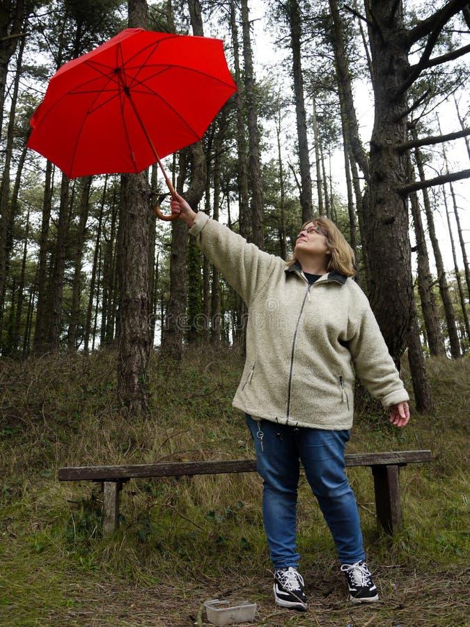 Donna che sostiene un ombrello rosso fotografie stock libere da diritti