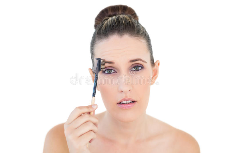 Donna che spazzola il suo sopracciglio che esamina colpito la macchina fotografica fotografia stock
