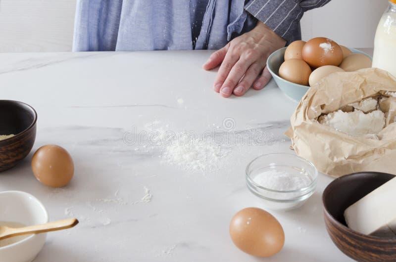 Donna che spolvera il tavolo da cucina con farina prima dell'impastamento della pasta Varie componenti per cuocere sulla tavola b fotografie stock libere da diritti