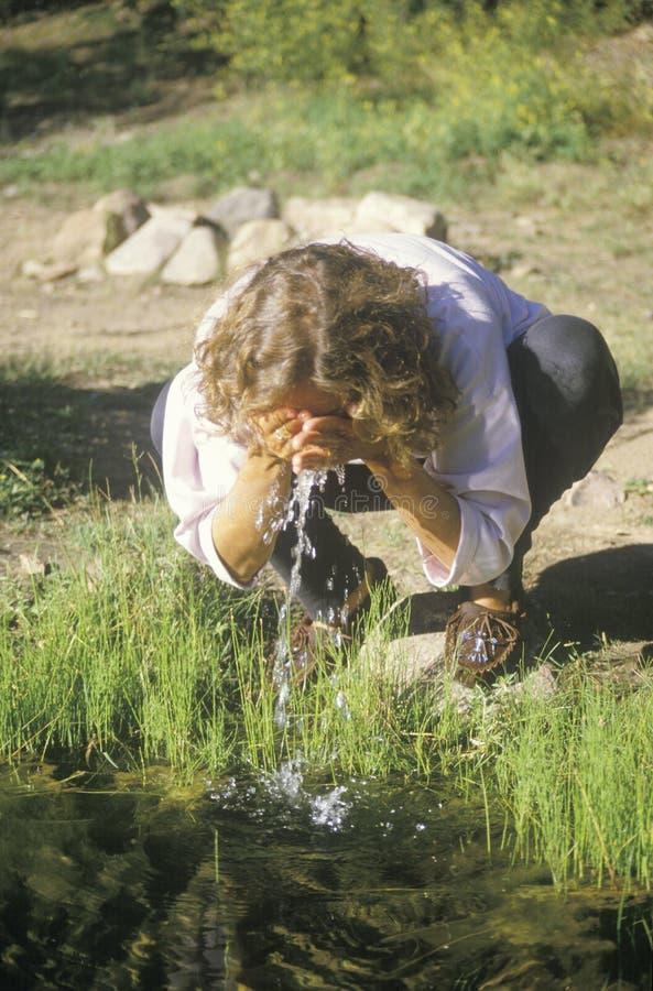 Donna che spruzza una certa acqua pulita sul suo fronte da un fiume fotografia stock libera da diritti