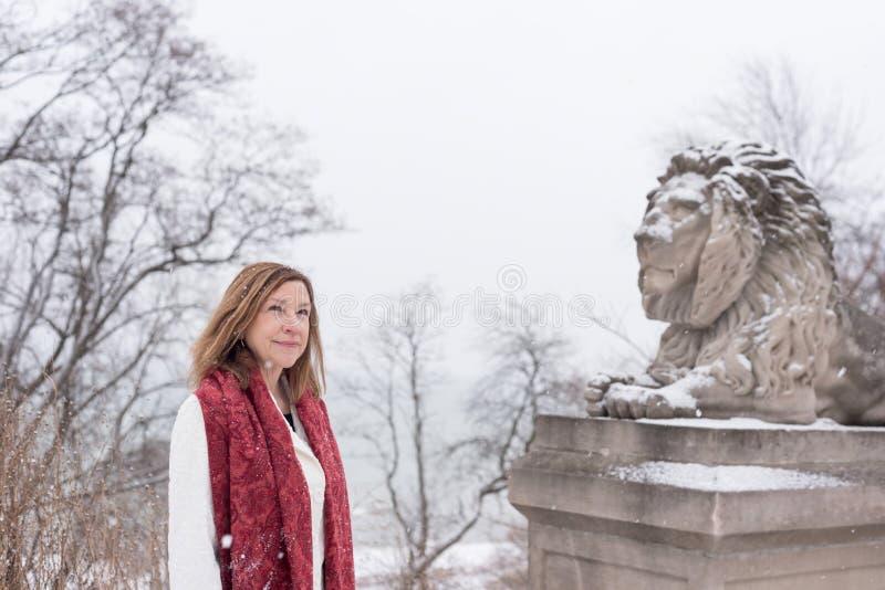 Donna che sta accanto al leone di pietra nel parco della città con la caduta della neve fotografie stock