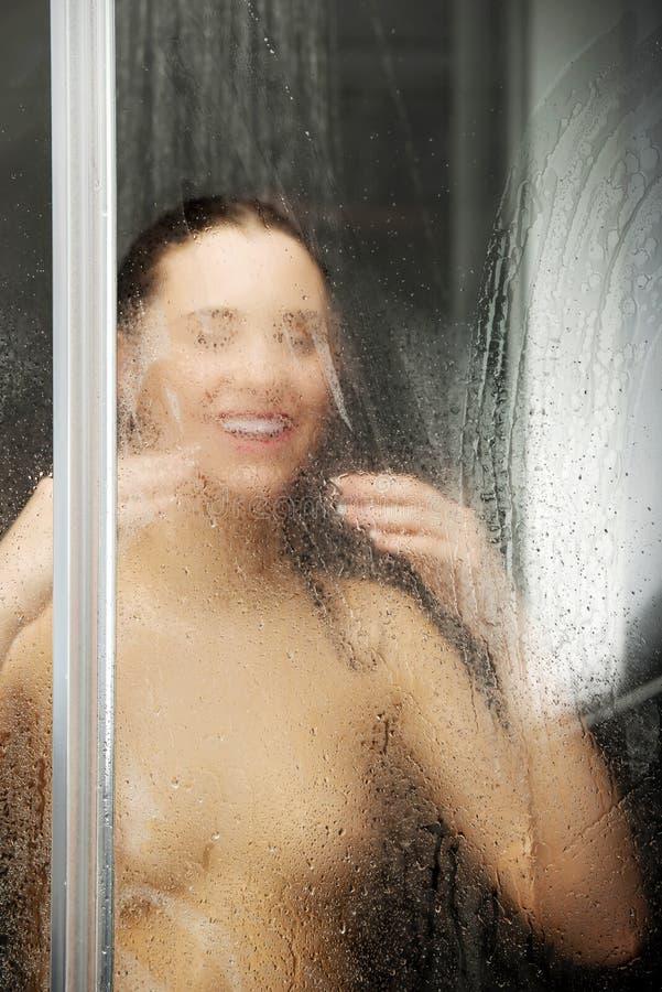 Donna che sta alla doccia immagine stock