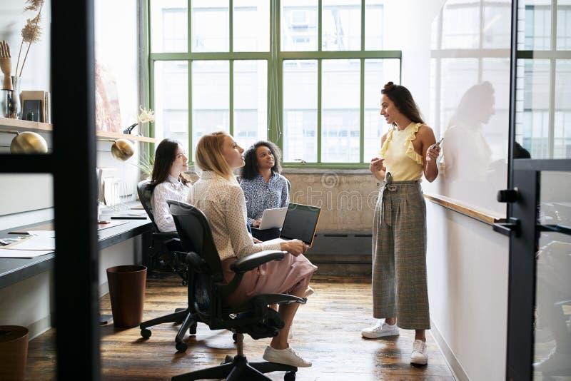 Donna che sta alla lavagna in una riunione con il gruppo femminile immagine stock