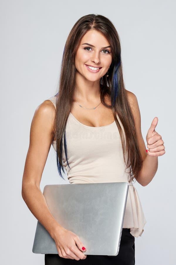 Donna che sta con il computer portatile chiuso fotografia stock libera da diritti
