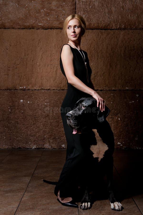 Donna che sta con un cane fotografie stock libere da diritti