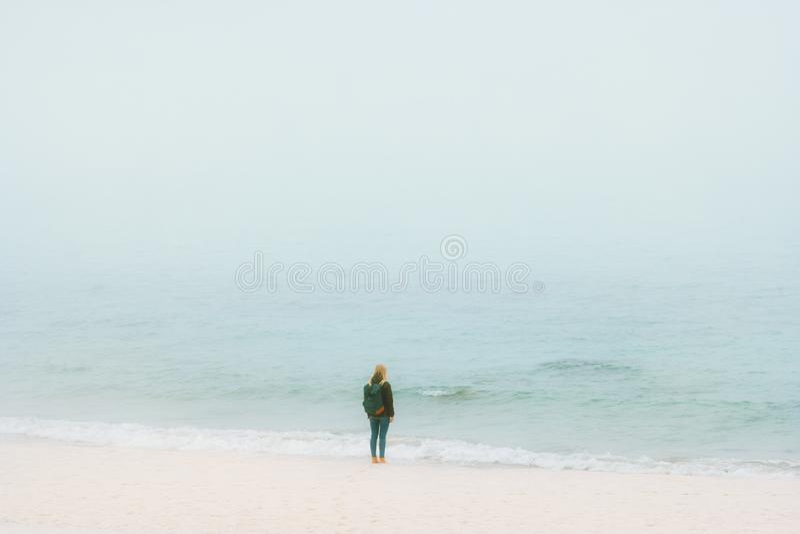 Donna che sta da solo sulla spiaggia che pensa con la vista di oceano nebbiosa fotografie stock libere da diritti