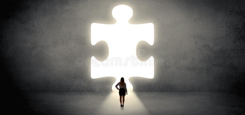 Donna che sta davanti ad un grande pezzo di puzzle fotografia stock libera da diritti