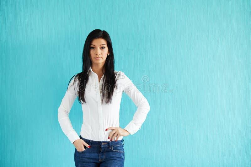 Donna che sta davanti alla parete del turchese immagine stock